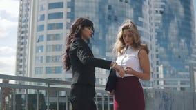 Due donne di affari prendono un appuntamento ed esaminano l'orologio ritratto degli uomini d'affari su un fondo di moderno stock footage