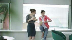 Due donne di affari su un intervallo di pranzo alla finestra nel self-service che mangiano alimento cinese e che bevono caffè La  video d archivio