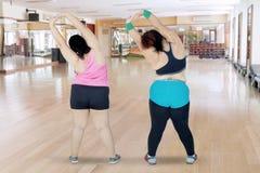 Due donne di peso eccessivo che allungano insieme le mani Fotografie Stock