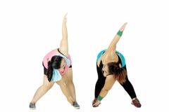 Due donne di peso eccessivo che fanno allungamento sullo studio Fotografie Stock