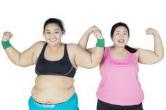 Due donne di peso eccessivo che mostrano il loro muscolo del braccio Immagine Stock