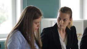 Due donne discutono lavorare i dettagli a vicenda in ufficio stock footage