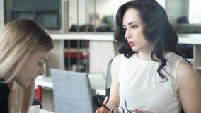 Due donne discutono qualcosa che si siede alla tavola in ufficio video d archivio