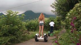 Due donne e guida durante il giro segway in colline, nuvolose archivi video