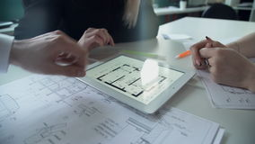 Due donne e l'uomo discutono il progetto architettonico in ufficio facendo uso del computer portatile stock footage
