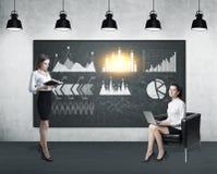 Due donne e sei grafici Immagini Stock
