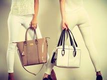 Due donne esili dentro con le borse delle borse di cuoio Fotografie Stock