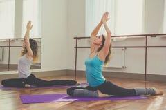 Due donne esili stanno facendo l'allungamento per le gambe Fotografia Stock