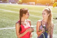 Due donne felici che bevono frullato di verdure dopo il runnin di forma fisica Fotografia Stock
