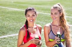 Due donne felici che bevono frullato di verdure dopo il runnin di forma fisica Immagine Stock Libera da Diritti