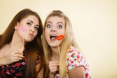 Due donne felici che tengono le labbra false sul bastone Fotografia Stock