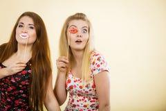 Due donne felici che tengono le labbra false sul bastone Immagine Stock