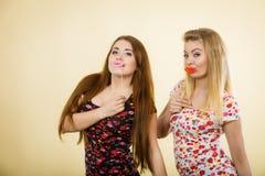 Due donne felici che tengono le labbra false sul bastone Fotografia Stock Libera da Diritti