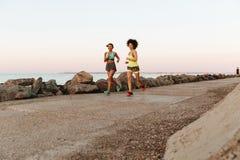 Due donne felici di forma fisica che corrono all'aperto Fotografia Stock