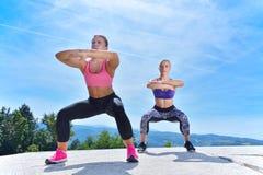 Due donne graziose che allungano in un parco prima dell'iniziare una sessione di allenamento Fotografie Stock Libere da Diritti