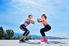 Due donne graziose che allungano in un parco prima dell'iniziare una sessione di allenamento Immagini Stock