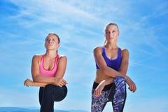 Due donne graziose che allungano in un parco prima dell'iniziare una sessione di allenamento Immagine Stock