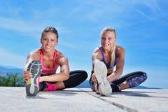 Due donne graziose che allungano in un parco prima dell'iniziare una sessione di allenamento Fotografia Stock