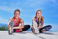 Due donne graziose che allungano in un parco prima dell'iniziare una sessione di allenamento Fotografia Stock Libera da Diritti