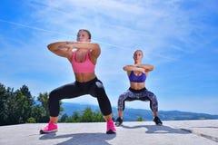 Due donne graziose che allungano in un parco prima dell'iniziare una sessione di allenamento Immagini Stock Libere da Diritti