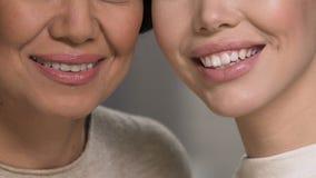 Due donne graziose che dimostrano sorriso perfetto, cura di odontoiatria, stile di vita di salute archivi video