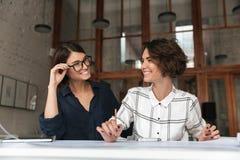 Due donne graziose felici che parlano dalla tavola Fotografia Stock Libera da Diritti