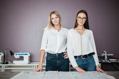 Due donne graziose Smart di aspetto che portano le camice bianche stanno controllando la tavola di cucito Modo, l'officina del sa fotografia stock