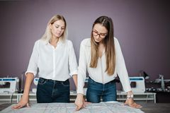 Due donne graziose Smart di aspetto che portano le camice bianche stanno pendendo sopra la tavola di cucito Modo, l'officina del  fotografia stock libera da diritti