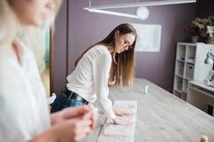 Due donne graziose Smart di aspetto che portano le camice bianche stanno pendendo sopra la tavola di cucito Modo, l'officina del  immagine stock libera da diritti