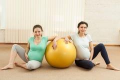Due donne incinte stanno sedendo vicino alla palla Fotografie Stock