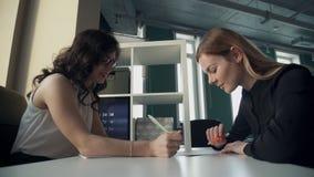 Due donne lavorano con alcuni documenti, scrivono i rapporti in ufficio archivi video
