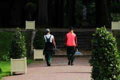 Due donne lavorarici camminano lungo il percorso del parco per elaborare le piste della ghiaia Lavoro di autunno, parco di Gatcin fotografia stock