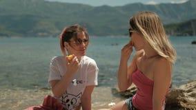 Due donne mangiano la frutta e comunicano su una spiaggia soleggiata archivi video