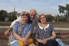 Due donne mature si siedono su un banco, dietro loro sguardi di un uomo fuori Fotografia Stock Libera da Diritti