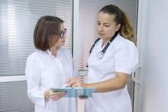 Due donne medico e chirurgo che parla all'ospedale sui precedenti della porta fotografie stock libere da diritti