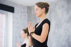 Due donne in palestra classificano, esercizio di rilassamento o classe di yoga fotografia stock libera da diritti