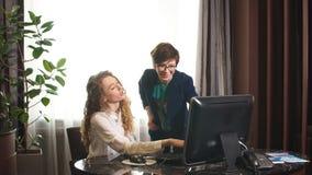 Due donne positive che lavorano con il computer stock footage