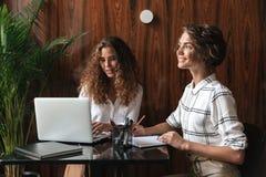 Due donne ricce che lavorano dalla tavola Fotografia Stock