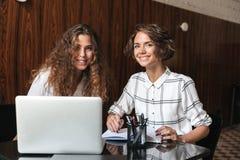Due donne ricce sorridenti che lavorano dalla tavola Fotografia Stock