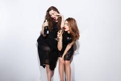 Due donne sexy in champagne bevente del vestito da notte Immagini Stock