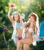 Due donne sexy con le attrezzature provocatorie che mettono i vestiti per asciugarsi in sole Giovani femmine sensuali che ridono  Immagine Stock
