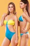 Due donne sexy in swimwear che posa sul fondo arancio Ente perfetto Concetto della pubblicità di estate del bikini Immagini Stock Libere da Diritti