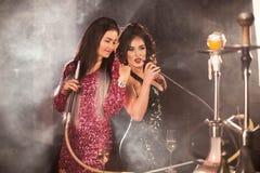 Due donne sexy in una barra di shisha o in un narghilé di fumo del ristorante Immagini Stock