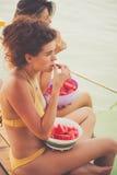 Due donne si siedono dal fiume in bikini godono di di mangiare le fette dell'anguria Fotografia Stock