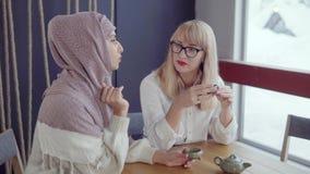Due donne sorridente che spendono tempo in un caffè video d archivio