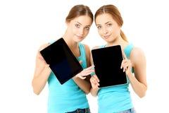 Due donne sorridenti che tengono il computer della compressa fotografie stock libere da diritti