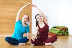 Due donne sorridenti fanno l'allungamento dell'esercitazione nel randello di sport Ginnastica di forma fisica Fotografie Stock Libere da Diritti