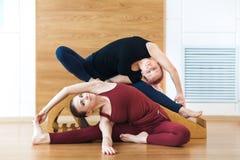 Due donne sorridenti fanno l'allungamento dell'esercitazione nel randello di sport Ginnastica di forma fisica Fotografia Stock