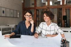 Due donne sorridenti graziose che si siedono dalla tavola Immagini Stock