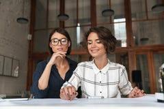 Due donne sorridenti graziose di bellezza che si siedono dalla tavola Fotografia Stock Libera da Diritti